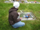 Carly at Palfreyman Plot, placing wildflowers on her ancestors' headstones