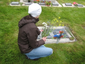 Carly at Palfreyman Plot, placing wildflowers on her ancestors' headstones